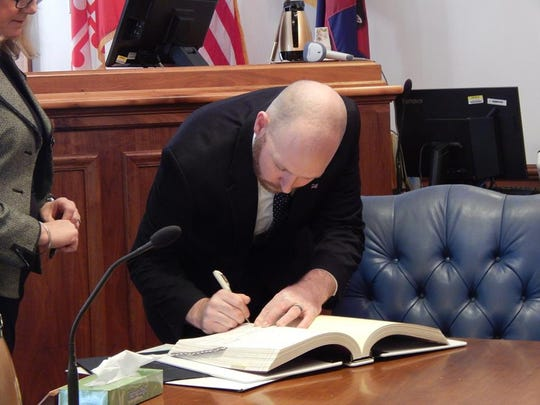 The new interim state's attorney for Worcester County, William H. McDermott, signs the paperwork after taking his oath of office.