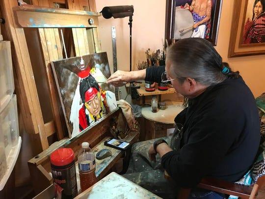 El Paso artist Bert Saldana works on one of his Southwest paintings in his studio Saturday in San Elizario.