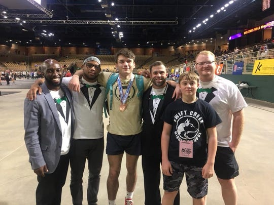 Lincoln wrestling coaches, including new National Wrestling Coaches Association Hall of Fame member Mike Crowder hang with 170-pound third-place finisher Justin Grant.