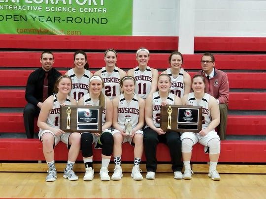 The UW-Marathon County women's basketball team pose with conference and state championship trophies at the state tournament in Wisconsin Dells on March 3.