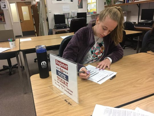 Senior Alyssa Russell, 18, registers to vote during a registration drive at Central Kitsap High School on Wednesday. The drive was held by student leaders in connection with the national observance of the one-month anniversary of the Parkland school shooting.