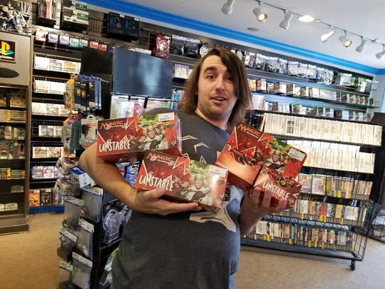 Tournament organizer Cameron Ellard stocks up on Magic cards for an upcoming tournament.