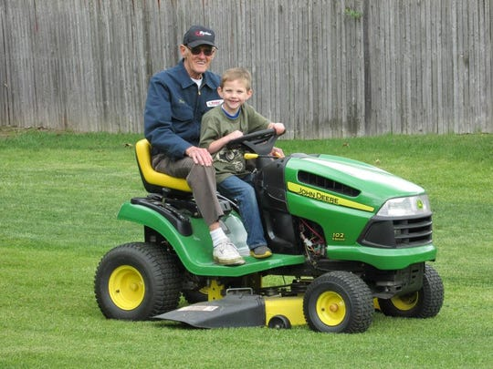 Donald Major rides a tractor along with his great granson,