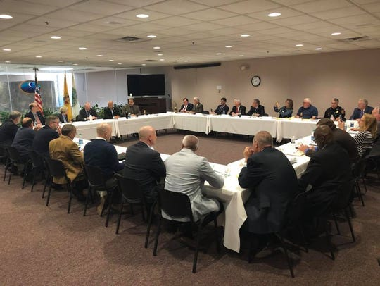 Gov. Phil Murphy, far left center, meets with about