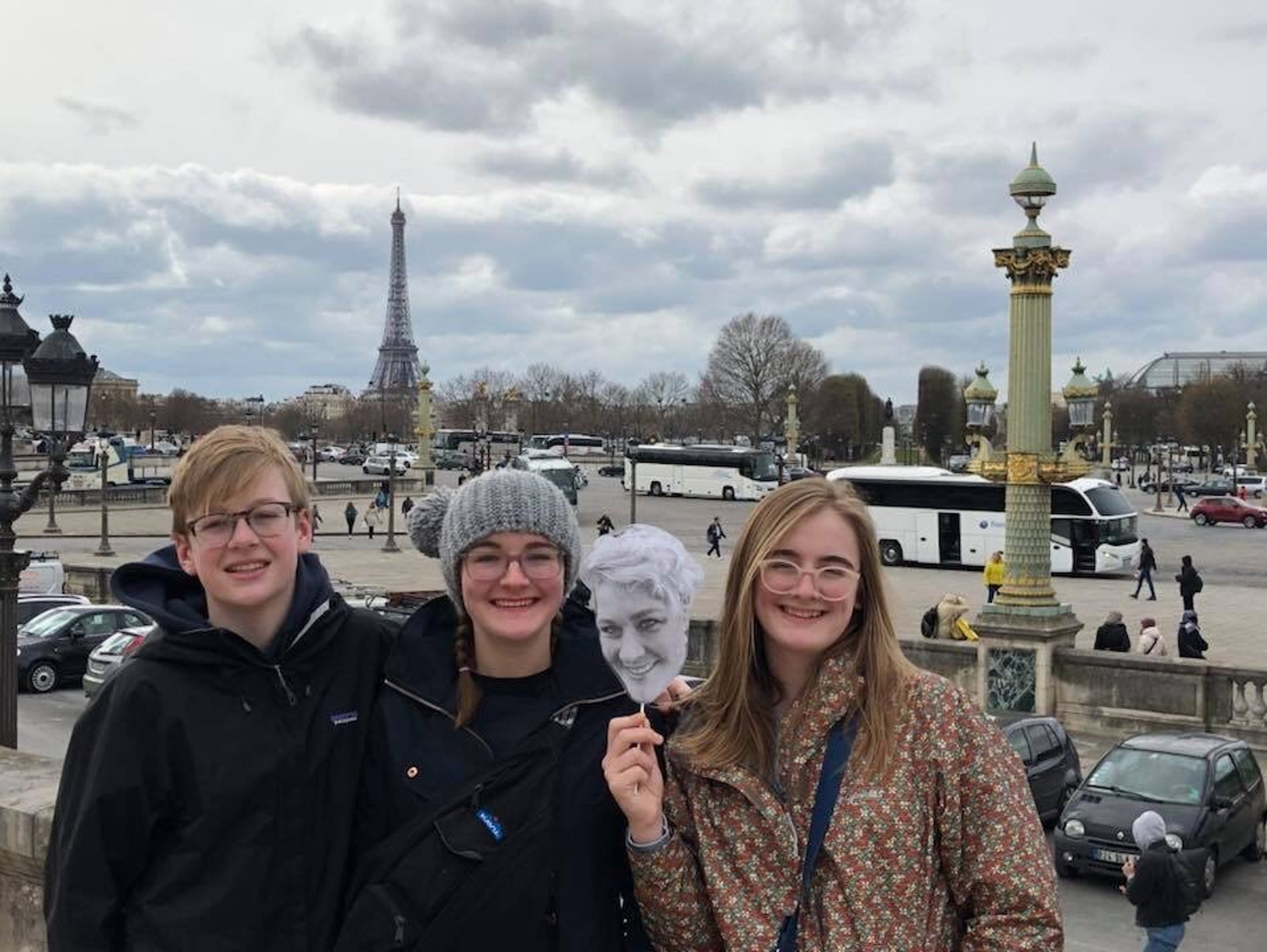 Emily Reese's children hold up a cutout of her face in France.