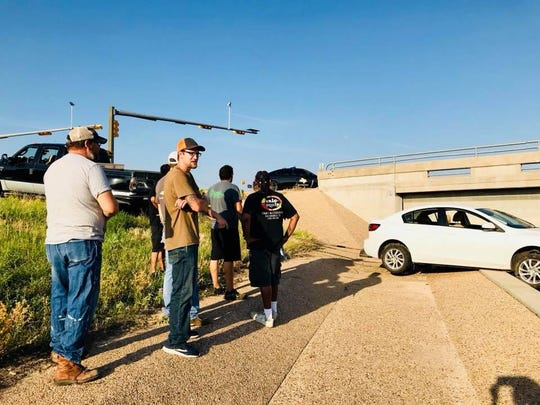 San Angelo Police have hailed seven citizens as 'heroes' after they saw a car dangling from the overpass off loop 306 and rushed in to save its occupants, a San Angelo mother and two children. June 1, 2018.