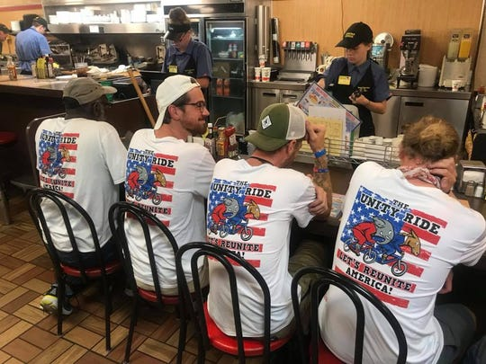 """Unity Ride crew members wear shirts that read """"Let's Reunite America"""" as they take a break at Waffle House in Kimball, Tenn. on June 8."""