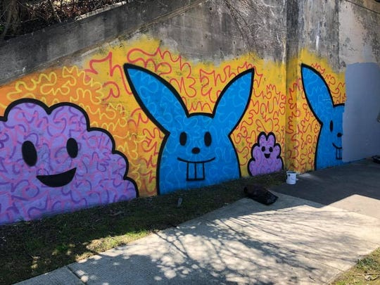 A mural under a railroad bridge on Farnum Avenue in Royal Oak, created by Carl Oxley III, gets painted over.