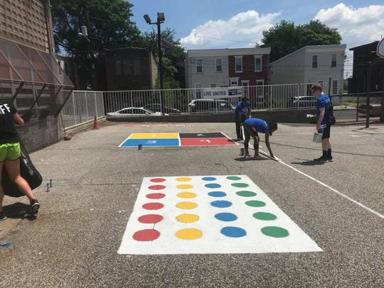 Volunteers paint outside the playground of U.S Wiggins
