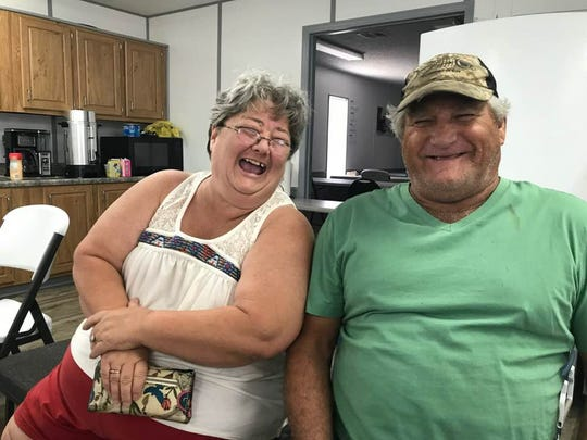 Eastpoint neighbors Bonnie Langley and Billy Dalton share a laugh as they apply for state emergency assistance.