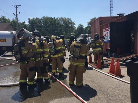 Firefighters line up to enter the flashover fire bin.