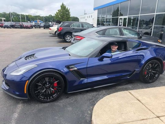 Nic Manion sits in his new Corvette.