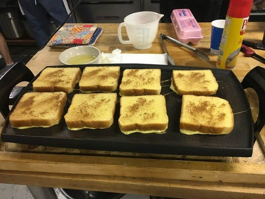 French toast being prepared on a griddle at the First