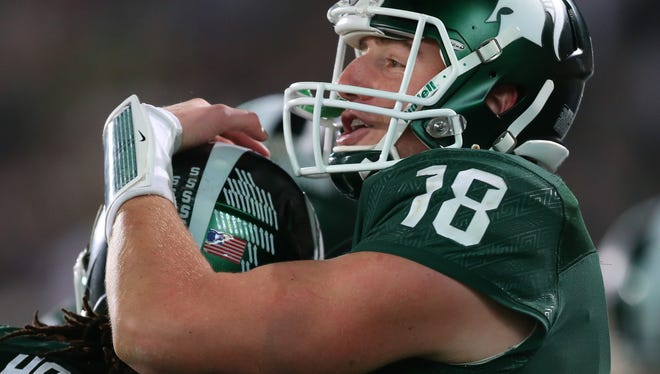 Michigan State's Connor Cook celebrates with Gerald Holmes after a touchdown against Indiana during the second half Saturday.