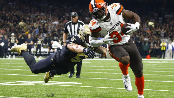 Cleveland Browns running back Carlos Hyde (34) runs past New Orleans Saints linebacker Manti Te'o on his way to scoring a touchdown during the second half of an NFL football game in New Orleans on Sept. 16, 2018.