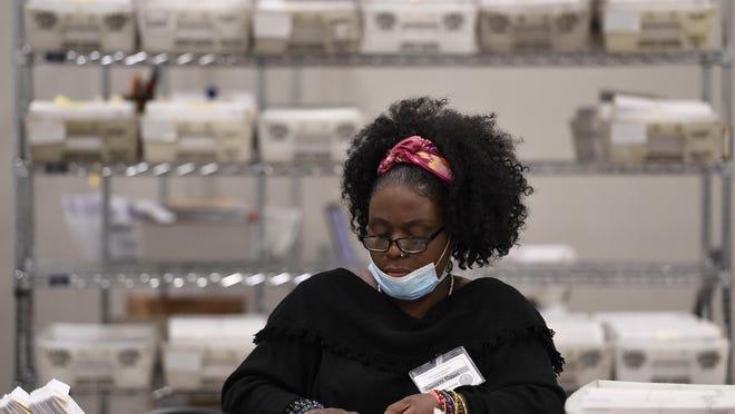 Cobb County Election officials handle ballots during an audit, Monday, Nov. 16, 2020, in Marietta, Ga.