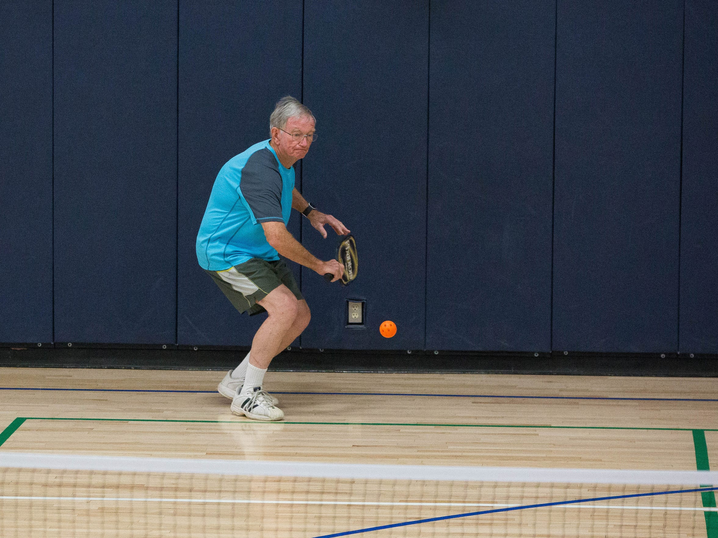 Paul Turner moves into hit a ball during a pickleball