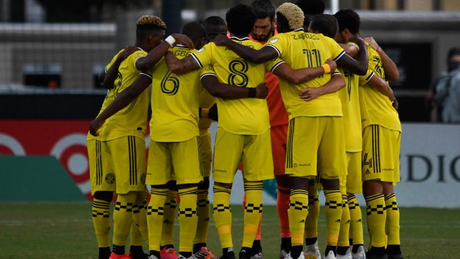 Crew starters huddle up prior to a game against Atlanta United on July 21 in the MLS is Back tournament. The Crew outscored its opponents by a combined 7-0 in the group stage.