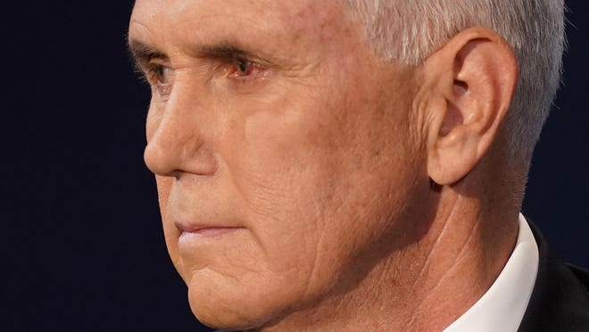 Vice President Mike Pence looks at Democratic vice presidential candidate Sen. Kamala Harris, D-Calif., during the vice presidential debate Wednesday, Oct. 7, 2020, at Kingsbury Hall on the campus of the University of Utah in Salt Lake City.