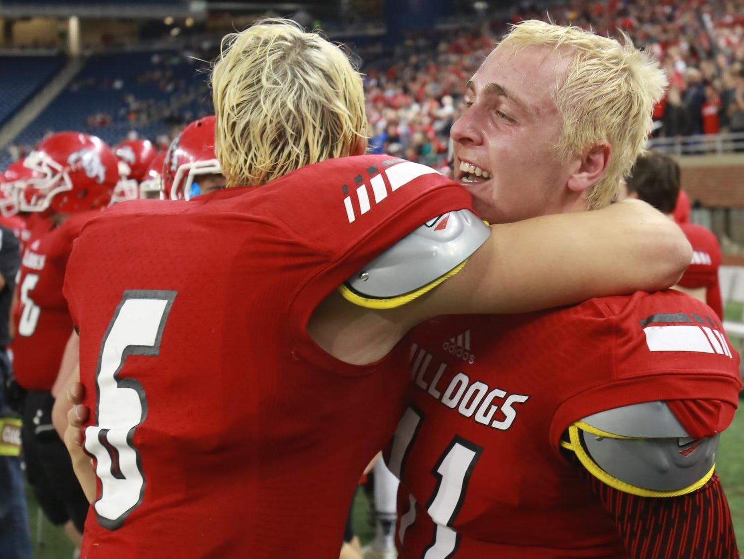 Romeo QB Paul Hurley, right, hugs John Houbeck after defeating Detroit Cass Tech, 41-27, during the Division 1 finals at Ford Field in Detroit on Saturday.