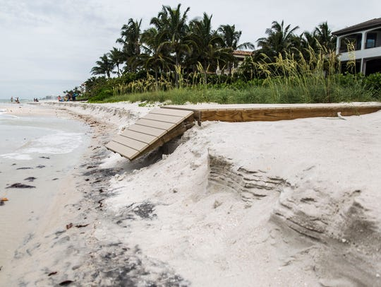 A private walkway lays broken where the shore is eroded