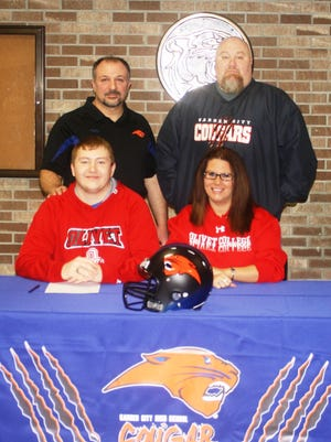 Easton Hayter is pictured with Garden City football coach Scott Murray and his parents, Jason and Samantha.