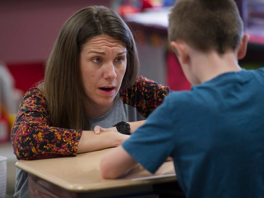 Libby Butcher, a third-grade teacher at Elberfeld Elementary School, works one-on-one with her students as they learn about telling time Tuesday morning, March 21, 2017.