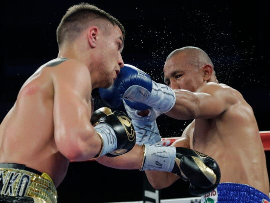 Orlando Salido, right, and, Vasyl Lomachenko, left, trade punches in a 12-round featherweight title bout on Saturday, March 1, 2014, in San Antonio. Salido won by split decision. (AP Photo/Eric Gay)