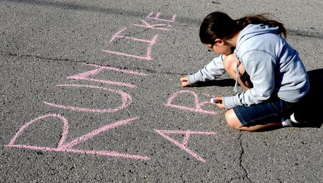 Clarissa LaPlante chalks a message for runners on Greene Avenue during the 2014 Bellin Run, Saturday, June 14, 2014.