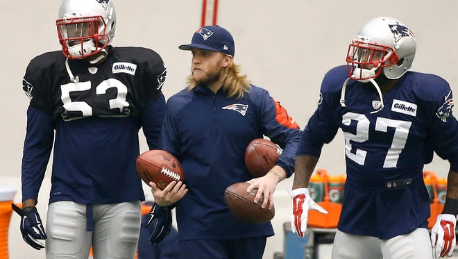 New England Patriots coaching assistant Steve Belichick holds footballs as New England Patriots strong safety Tavon Wilson (27) and linebacker Eric Martin (53) prepare to practice in Foxborough, Mass., last week.