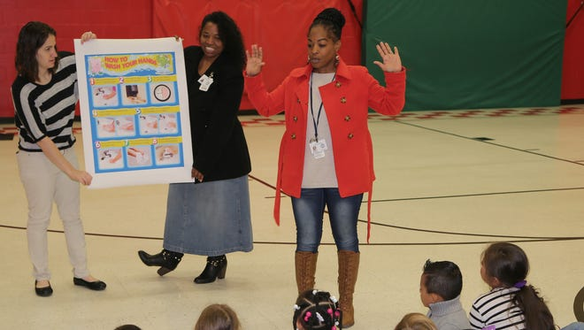 Beth Gray and Lisa Sweed, with the Sumner County Health Department, hold up a hand-washing diagram as Kimberly Bonds talks to students in Hendersonville.