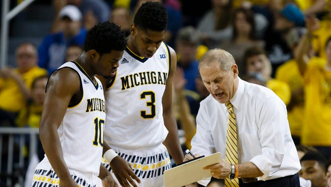 Nov 16, 2015; Michigan Wolverines head coach John Beilein talks to guard Derrick Walton Jr. (10) and guard Kameron Chatman (3) during the first half against the Elon Phoenix at Crisler Center.