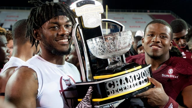 Troy University players carry the champions trophy after defeating Ohio in the Dollar General Bowl at Ladd-Peebles Stadium in Mobile, Ala. on Friday December 23, 2016.