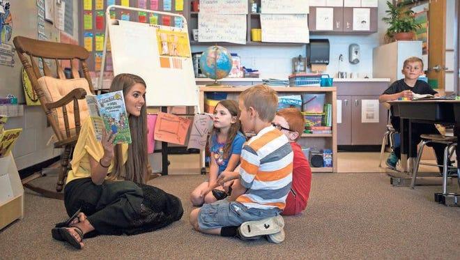"""First-grade teacher Brooke Rhodarmer reads """"A Green Green Garden"""" to her students at Leicester Elementary."""