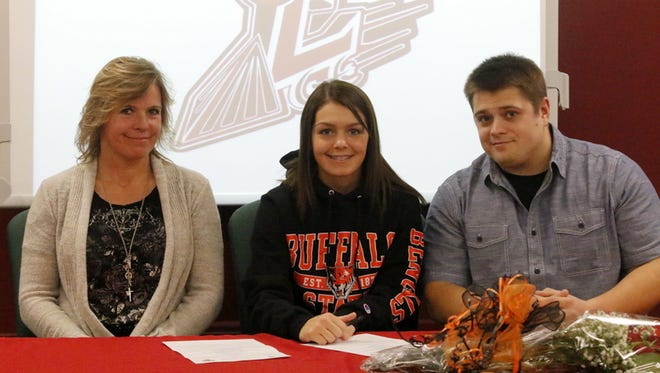 Elmira senior Ciera Sprague, center, signs a commitment letter to attend Buffalo State alongside her mom, Laurie Fleming, and her brother, Jesse Sprague, during a ceremony Thursday at Elmira High School.