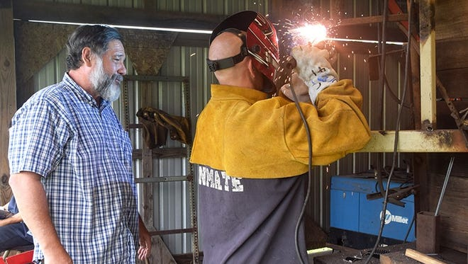 Road Prison Welding Instructor Danny Cain supervises an inmate participating in the George Stone Technical Center welding program at the Escambia County Road Prison.