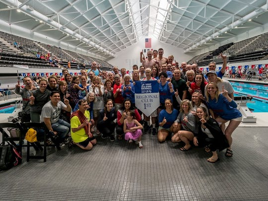 The Wisconsin Masters Aquatic Club captured the championship at the 2018 Spring Nationals. Fred Russell (holding banner), who coached at Pabst Farms in Oconomowoc and for Elmbrook, coached the team.