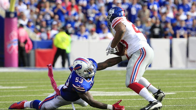 Giants running back Rashad Jennings, right, breaks a tackle attempt by Buffalo Bills outside linebacker Nigel Bradham on his way to score a touchdown during the second half of Sunday's game in Orchard Park. The Giants won 24-10 to even their record at 2-2.