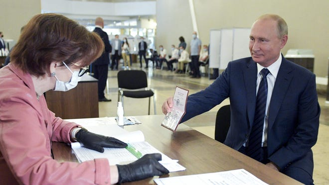 Russian President Vladimir Putin shows his passport to a member of an election commission as he arrives to take part in voting at a polling station in Moscow, Russia, Wednesday, July 1, 2020. The vote on the constitutional amendments that would reset the clock on Russian President Vladimir Putin's tenure and enable him to serve two more six-year terms is set to wrap up Wednesday.