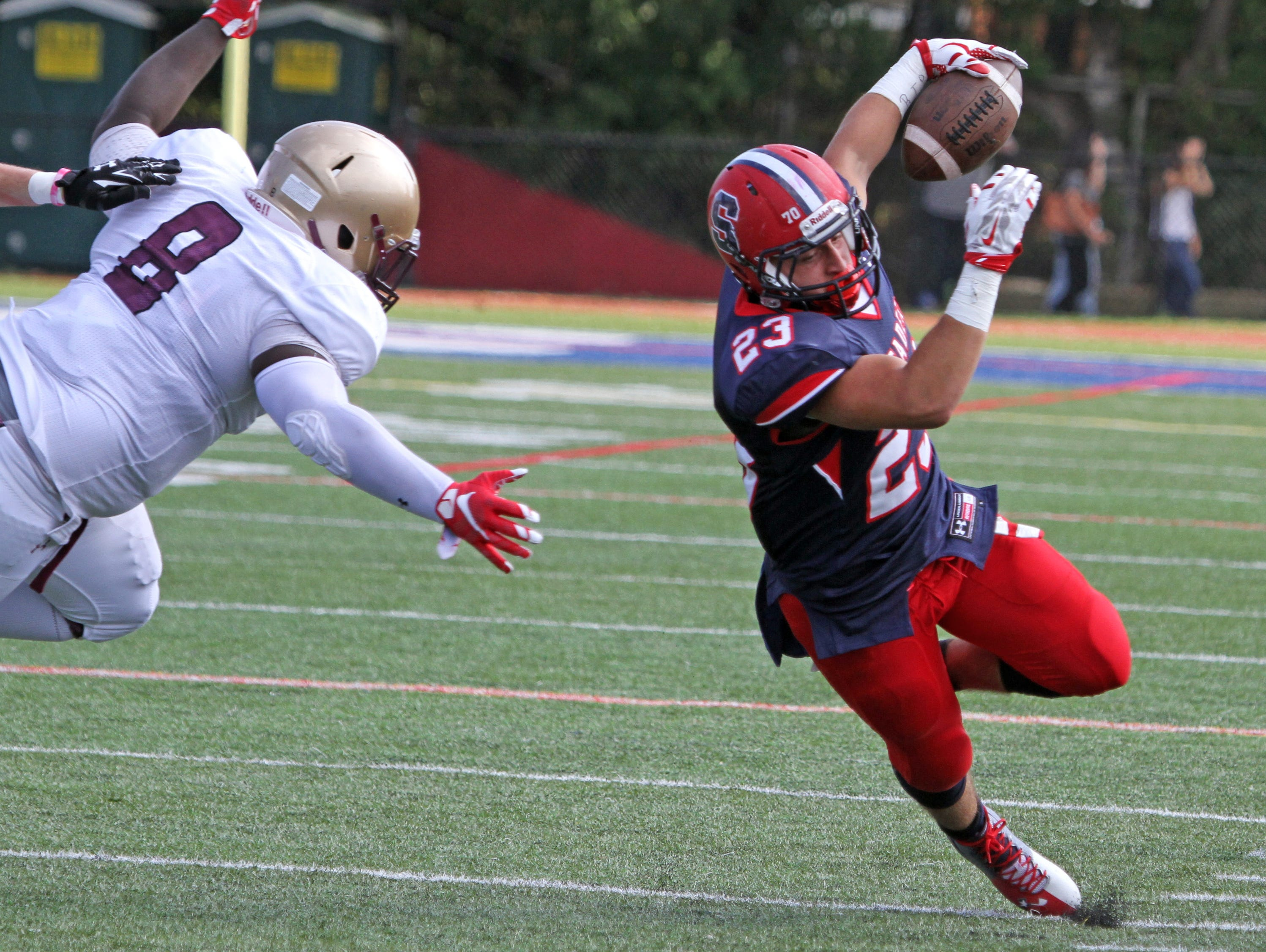 Stepinac's Antonio Giannico tries to evade Iona Prep's Darail McCormick during a varsity football game at Stepinac High School Sept. 19, 2015. Stepinac crushed Iona Prep 48-6.