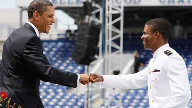 President Obama fist bumps a U.S. Naval Academy student about to receive his diploma in 2009.