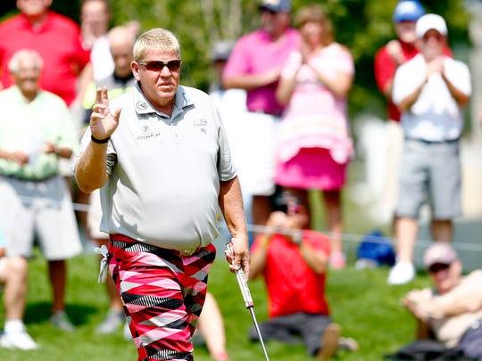 John Daly waves to the crowd after sinking a putt during