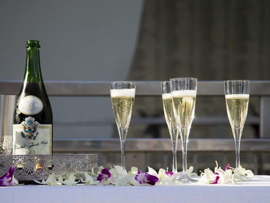 A bottle of sparkling wine signed by President  Ford sits next to glasses intended for survivors of the USS Arizona during a final toast ceremony on the USS Arizona Memorial at Pearl Harbor.