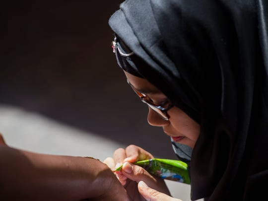 University of Tennessee student Keher Ony draws a henna
