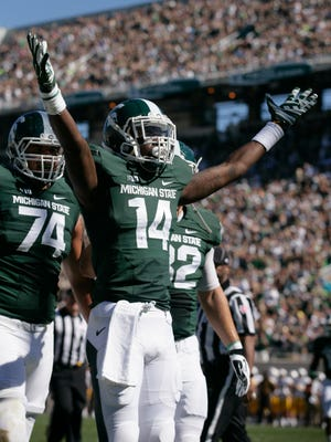 Michigan State's Tony Lippett (14) celebrates his touchdown reception against Wyoming as teammates Jack Conklin (74) and Josiah Price, right, move in to join him during the first quarter Saturday.