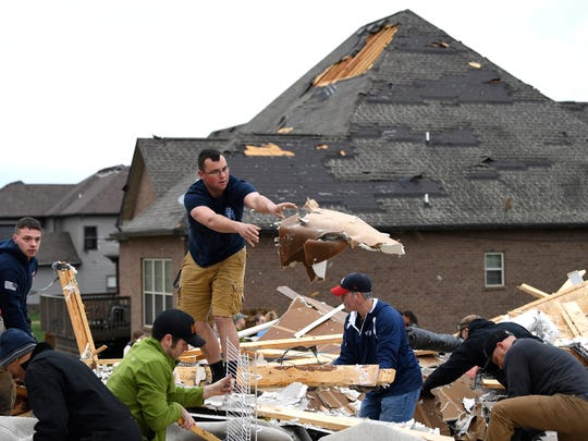 People work to clear debris after a fierce storm hit