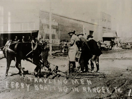 A man pulls passengers across the muddy street in Ranger during the oil boom in 1919.
