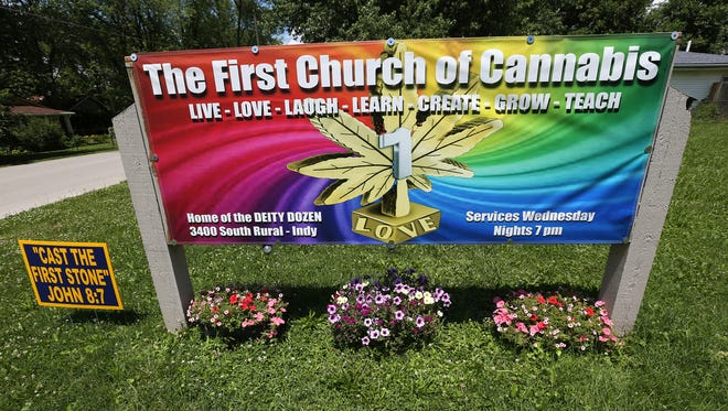 """Cast the first stone,"" from the biblical verse John 8:7, is seen, at left, in front of The First Church of Cannabis, Tuesday, June 23, 2015.  The sign was put there by founder Bill Levin.  The first service of the new church will be at noon on Wednesday, July 1, 2015."