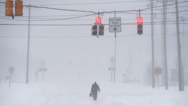 A lone figure walks along Memory Lane in Springettsbury Township during Saturday's snowstorm on Jan. 23, 2016.