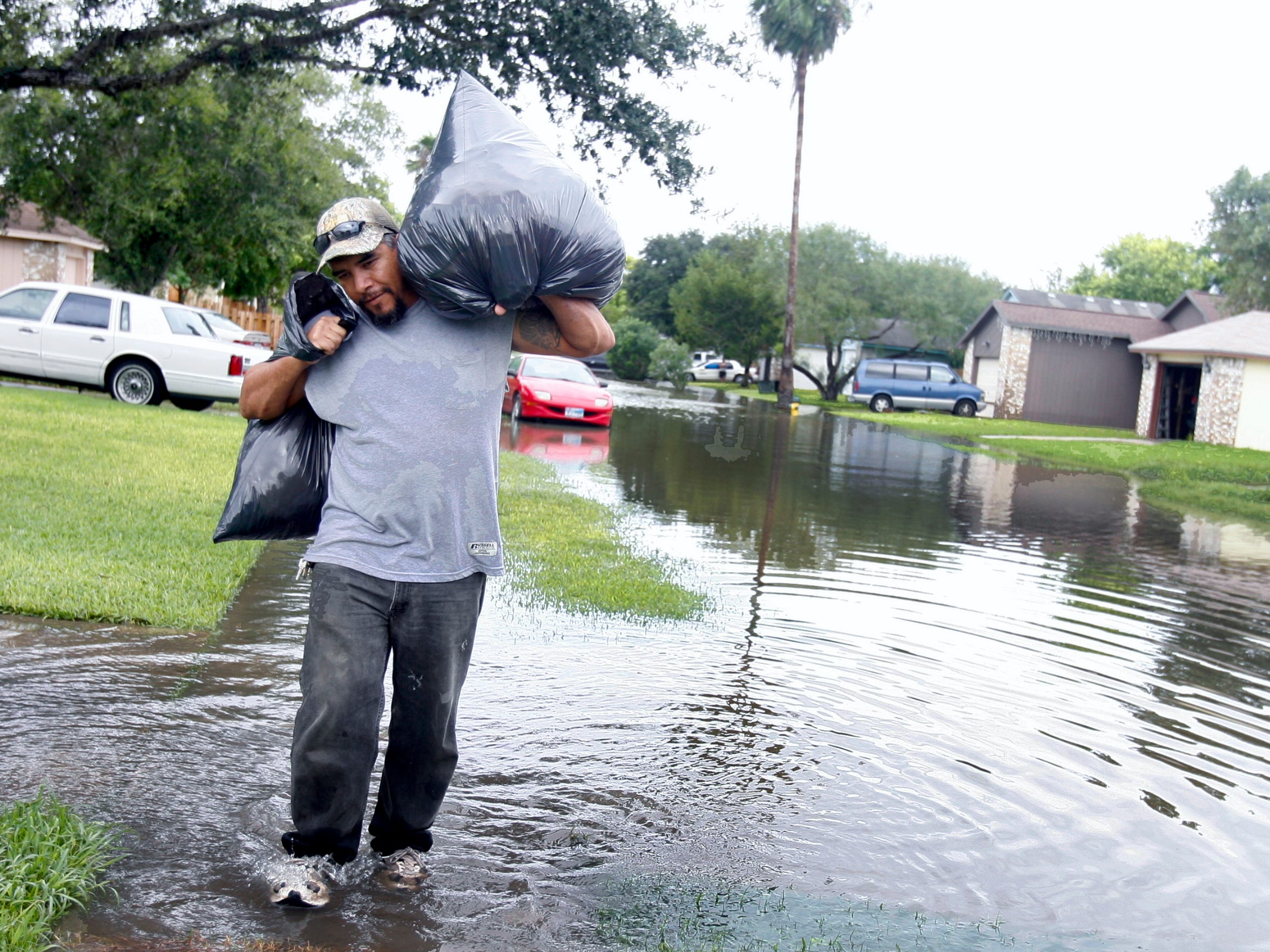 In this 2010 file photo, Joe Rocha carries garbage bags full of soggy belongings through Las Colonias subdivision. The subdivision, located near. Many residents reported they were up to their chests in water. In draft 2015 flood maps, part of the neighborhood is shown in a floodway and the remainder, in a floodplain. Revised maps are expected to be released this year.